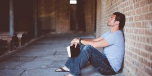 un hombre reflexionando apoyado en una pared